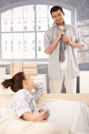 Young man dressing up in the morning, woman looking at him from bed, smiling at each other photo
