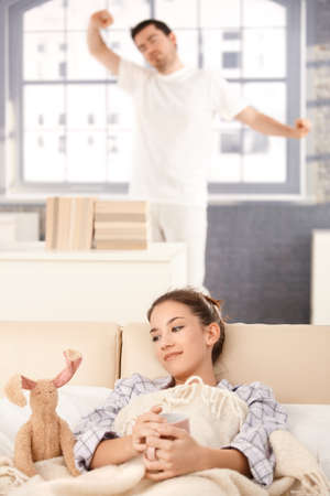 Young couple waking up in the morning, woman drinking tea, man stretching in the background. photo