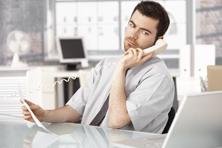 poner atencion: Joven empresario trabajan en la Oficina de brillante, utilizando equipo port�til, hablando por tel�fono. Foto de archivo