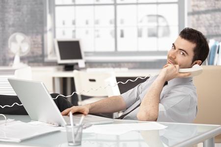 prestar atencion: Joven corredor de bolsa trabajo en Oficina brillante, usa portátil, hablando por teléfono.