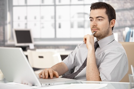 sitting at desk: Young businessman working in bright office, sitting at desk, using laptop.