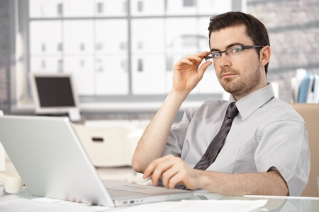 Young businessman working in bright office, sitting at desk, using laptop, wearing glasses. photo