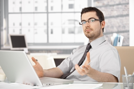 stockphoto: Young stock broker working in bright office, sitting at desk, using laptop, wearing glasses.