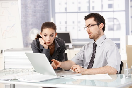 Young man and woman working together in office, looking at laptop, sitting at desk. photo