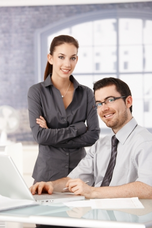 pair: Young colleagues working and smiling in bright office. Stock Photo