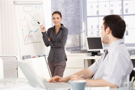 Young attractive female presenting in office over whiteboard, smiling. photo