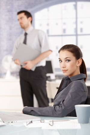 Portrait of young attractive businesswoman sitting at desk, businessman standing in the background. photo