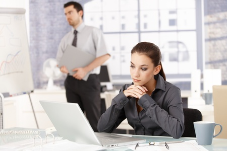 Young attractive woman sitting in office at desk, looking at laptop, man standing in background photo