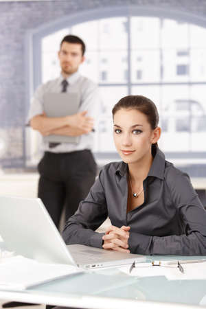 Portrait of young attractive businesswoman sitting at desk, businessman standing in the background. Stock Photo - 8556742