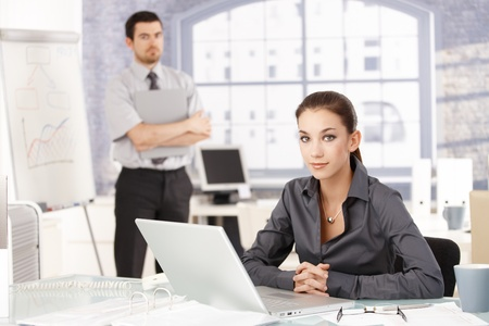 Young businessteam working in office, woman sitting at desk with laptop, man standing by whiteboard in the background. photo