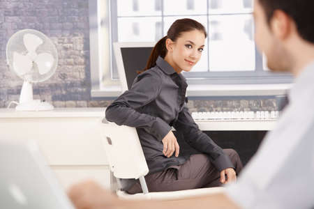 Young attractive businesswoman sitting at desk, turning back, smiling at her colleague. photo