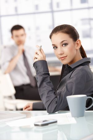 Portrait of young attractive businesswoman sitting at desk in office, smiling, man in the background. photo