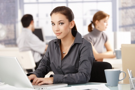 Young attractive businesswoman sitting at desk in office, colleagues working in the background. photo