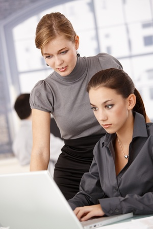 Young businesswomen working together in bright office, looking at laptop. photo