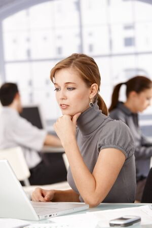 Young female office worker sitting at desk in office working on laptop, colleagues working in the background. Stock Photo - 8552009