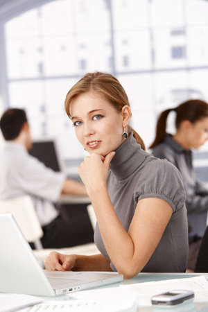 Young businesswoman sitting at desk in office working on laptop, colleagues working in the background. photo