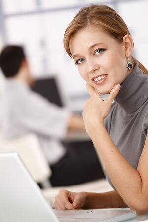 Young female working on laptop, sitting at desk in office, smiling. Stock Photo - 8549561