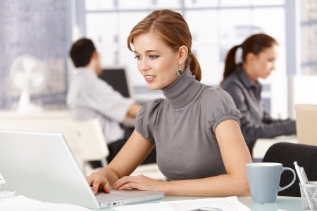 working women: Young woman working in office, sitting at desk, using laptop, smiling, colleagues working in background.