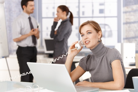 Young woman talking on phone in office, sitting at desk, using laptop, smiling, colleagues chatting in background. photo