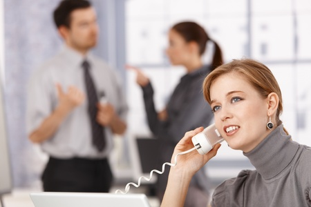 Young businesswoman talking on phone in office, colleagues chatting in background. photo