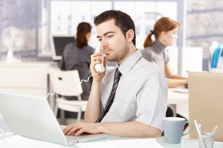 Young office worker sitting at desk in office, talking on phone, using laptop, women working in the background. Stock Photo - 8549434