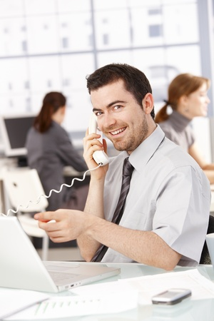 Happy businessman sitting at desk in office, talking on phone, using laptop, women working in the background.