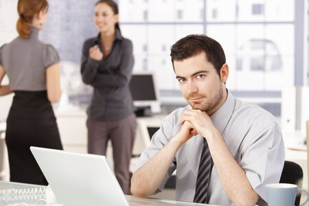 Happy business team having break in office, women chatting in background, man sitting at desk. Stock Photo - 8549474