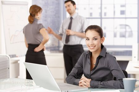 Attractive businesswoman smiling happily in office, sitting at desk, having laptop, colleagues chatting in background. photo