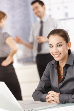 Young attractive female office worker sitting at desk with laptop, smiling, others chatting behind. Stock Photo - 8549505
