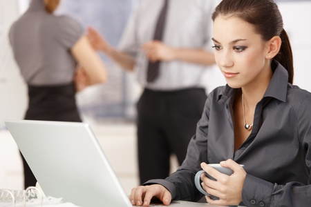 foreground: Young attractive woman working on laptop in office, colleagues standing in background.