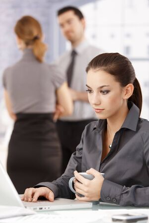 Young attractive female using laptop in office, colleagues chatting in background. photo