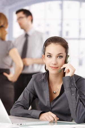 Young customer servicer sitting at desk, using headphones, young people chatting in background. Stock Photo - 8549573