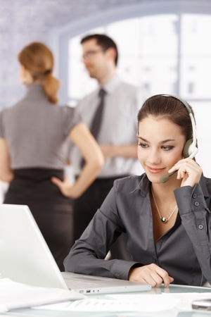 Young attractive dispatcher talking on headphones in office, young colleagues standing behind. Stock Photo - 8549481