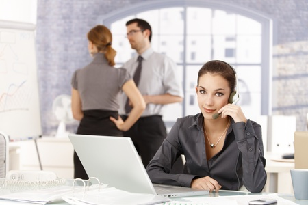 Young people working in office, woman with headset in the foreground, colleagues having discussion in the background. Stock Photo - 8556719