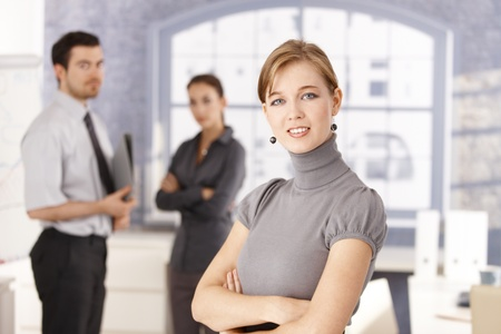 Portrait of young business team in office, attractive woman smiling in foreground. photo