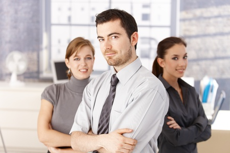 Young colleagues, one man, two women standing in bright office arms crossed, smiling. photo