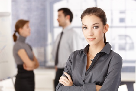 Young attractive office worker standing arms crossed in office, young businesspeople chatting in the background. photo