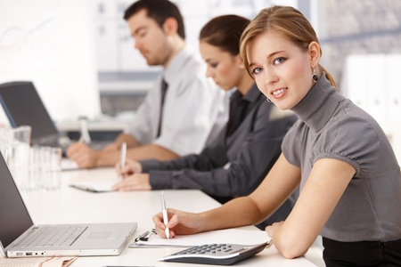 Young businesspeople sitting at meeting table in office, having business training, writing notes. Stock Photo - 8549659