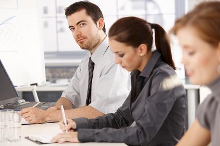 Oficina de jóvenes trabajadores tener formación empresarial, sentado en la reunión de la mesa, escribir notas. Foto de archivo