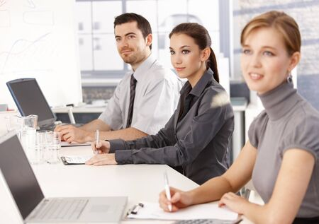 Young businessteam sitting at meeting table, listening presentation, writing notes. photo
