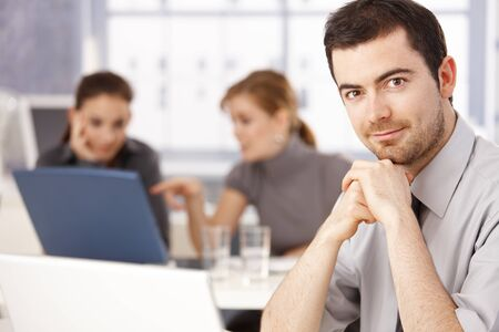 Portrait of young man sitting at meeting table, women working in the background. Stock Photo - 8558328