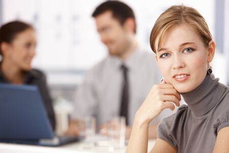 Portrait of young blond businesswoman sitting at table, others chatting behind. Stock Photo - 8552074