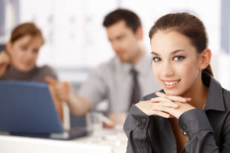 Portrait of attractive businesswoman sitting at meeting table, colleagues working in the background. photo