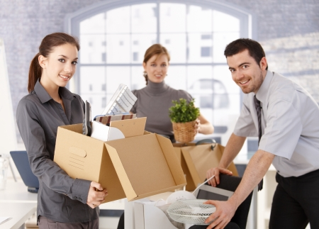 moving box: Young office workers moving office, unpacking boxes, smiling. Stock Photo