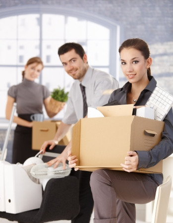 moving box: Happy businesspeople moving to new office, packing boxes, smiling. Stock Photo