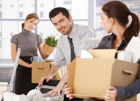 Young group of office workers moving to new office, unpacking boxes, smiling. Stock Photo - 8556726