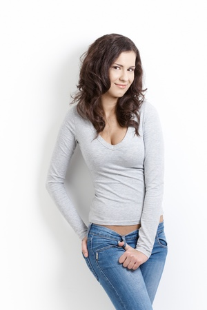 jeans girl: Young sexy girl posing over white background, smiling.