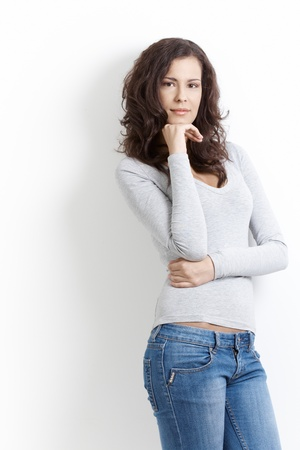 unsmiling: Young attractive woman standing over white background. Stock Photo