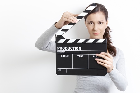 offish: Attractive young girl holding clapper board front of her face. Stock Photo