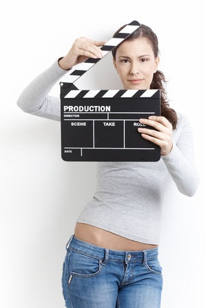 making face: Attractive young female holding clapper board in her hands, front of her face, smiling. Stock Photo